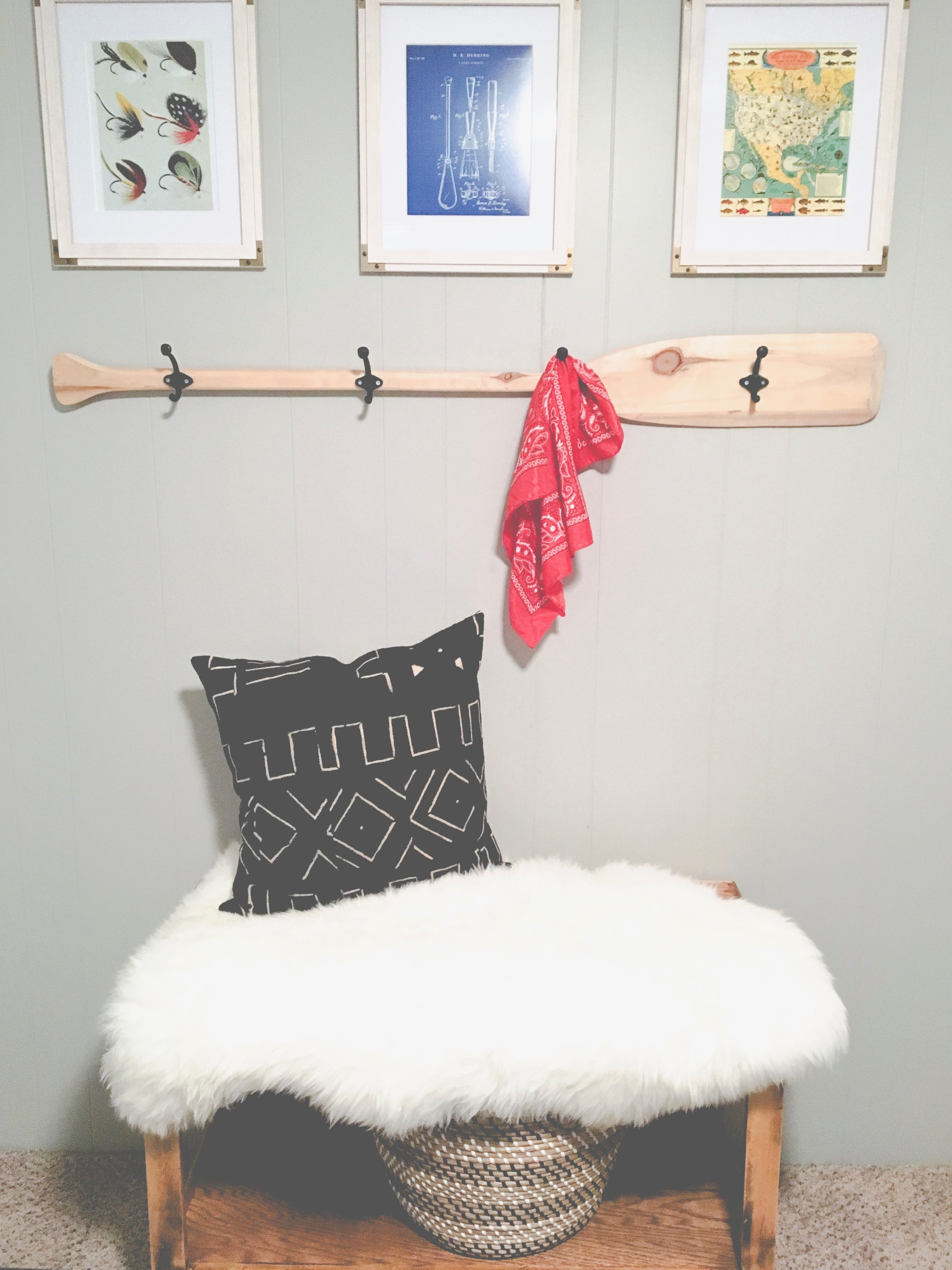 Our boring guest room gets a whole new modern cozy chic cabin look! Learn how to redecorate your guest room so it feels cozy and welcoming. This wooden oar hook and vintage fishing prints are a great touch.