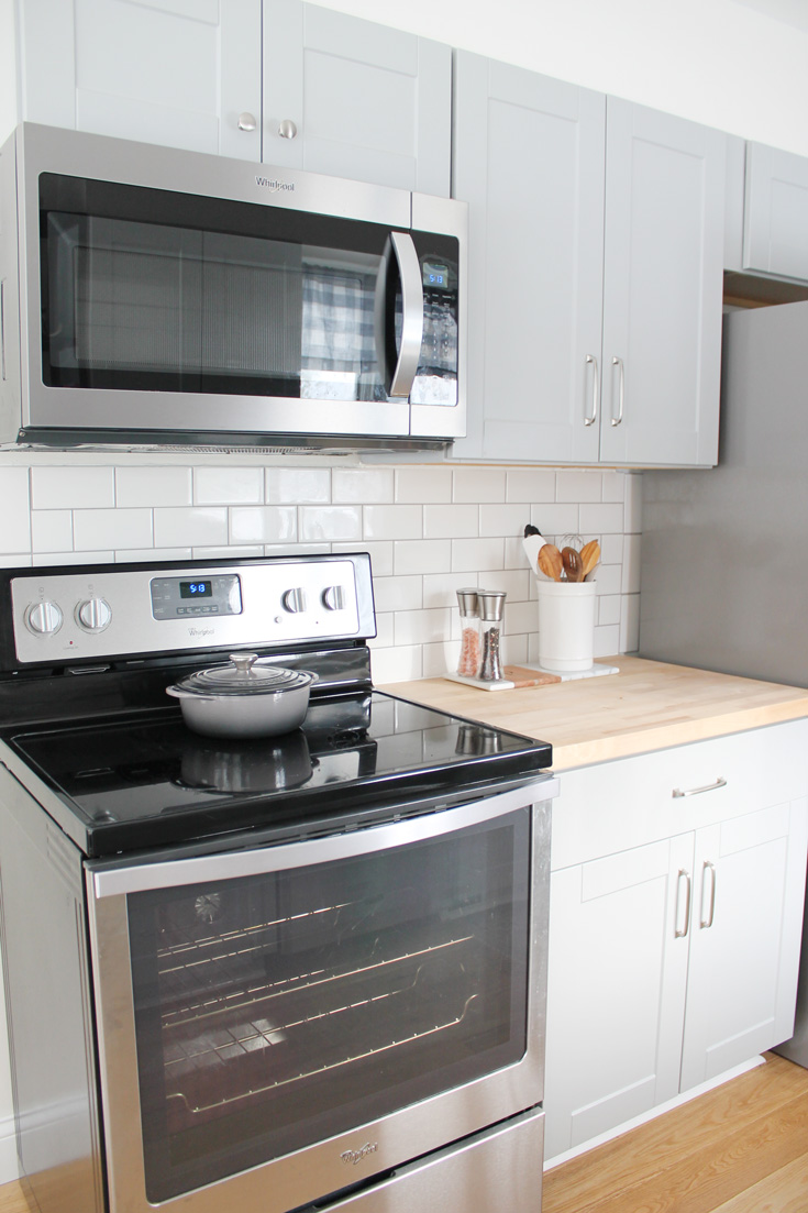 Our small kitchen remodel reveal on a budget with grey cabinets, oak wood flooring, stainless steel appliances, a farmhouse sink and more. Click to see the before and afters. You won't believe what it looked like before!