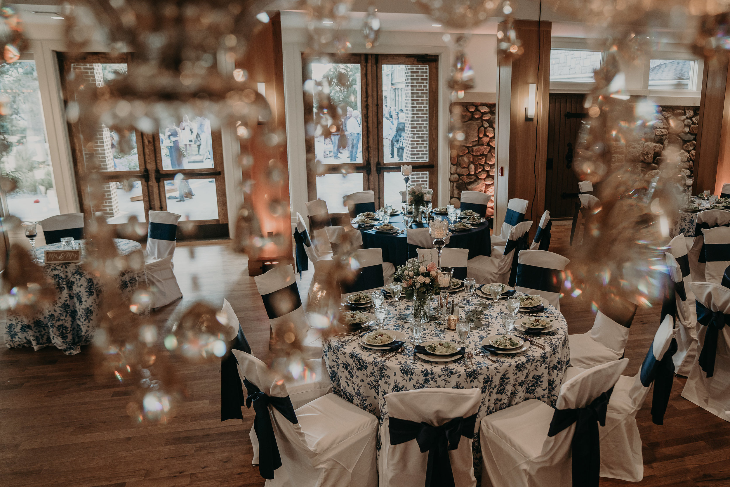 Image by  Lindy Hickman Photography   I love the use of accent linens here, they really make the space pop! Navy chair sashes bring it all together, in addition to simple floral displays and centerpieces at a variety of heights.