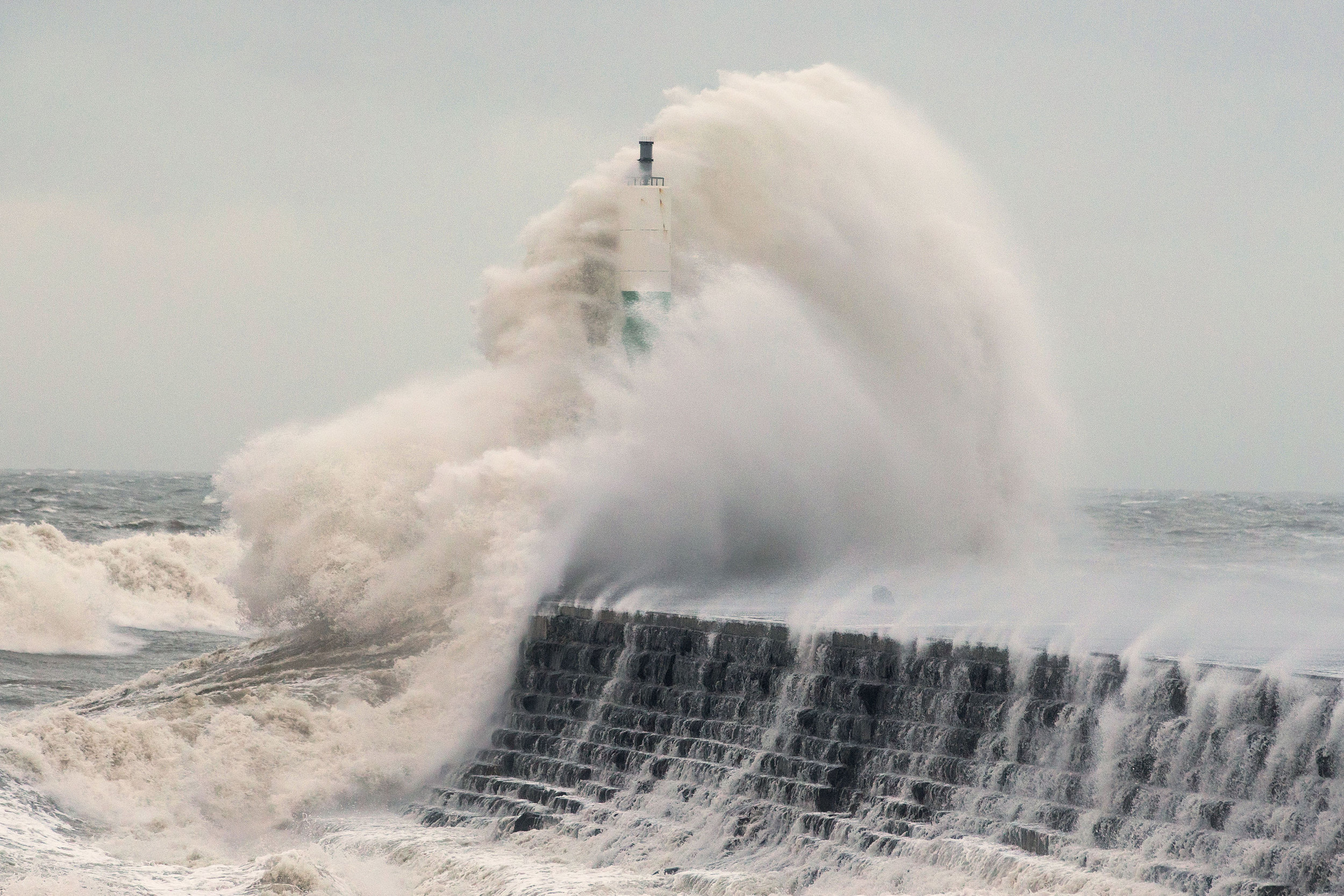 Waves crash over the stone jetty wall in Aberystwyth in west Wales as Storm Eleanor lashed the UK with violent storm-force winds of up to 100mph, leaving thousands of homes without power and hitting transport links