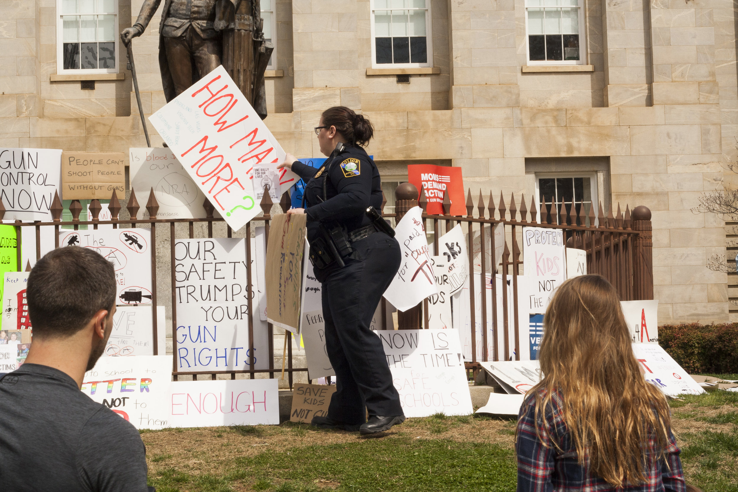 A police officer takes down signs saying it is litter as protesters observe.