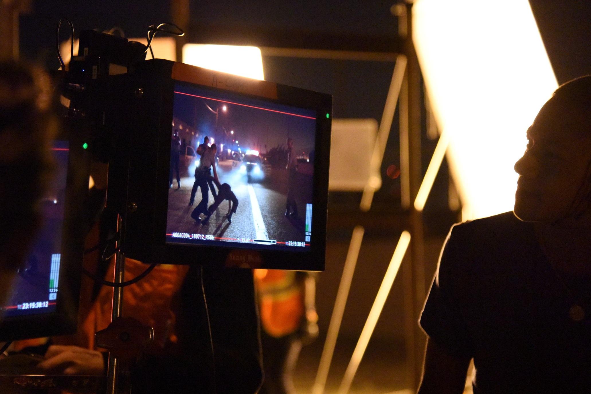 Actor  Brandon Soo Hoo  sneaks behind the monitors to watch playback.