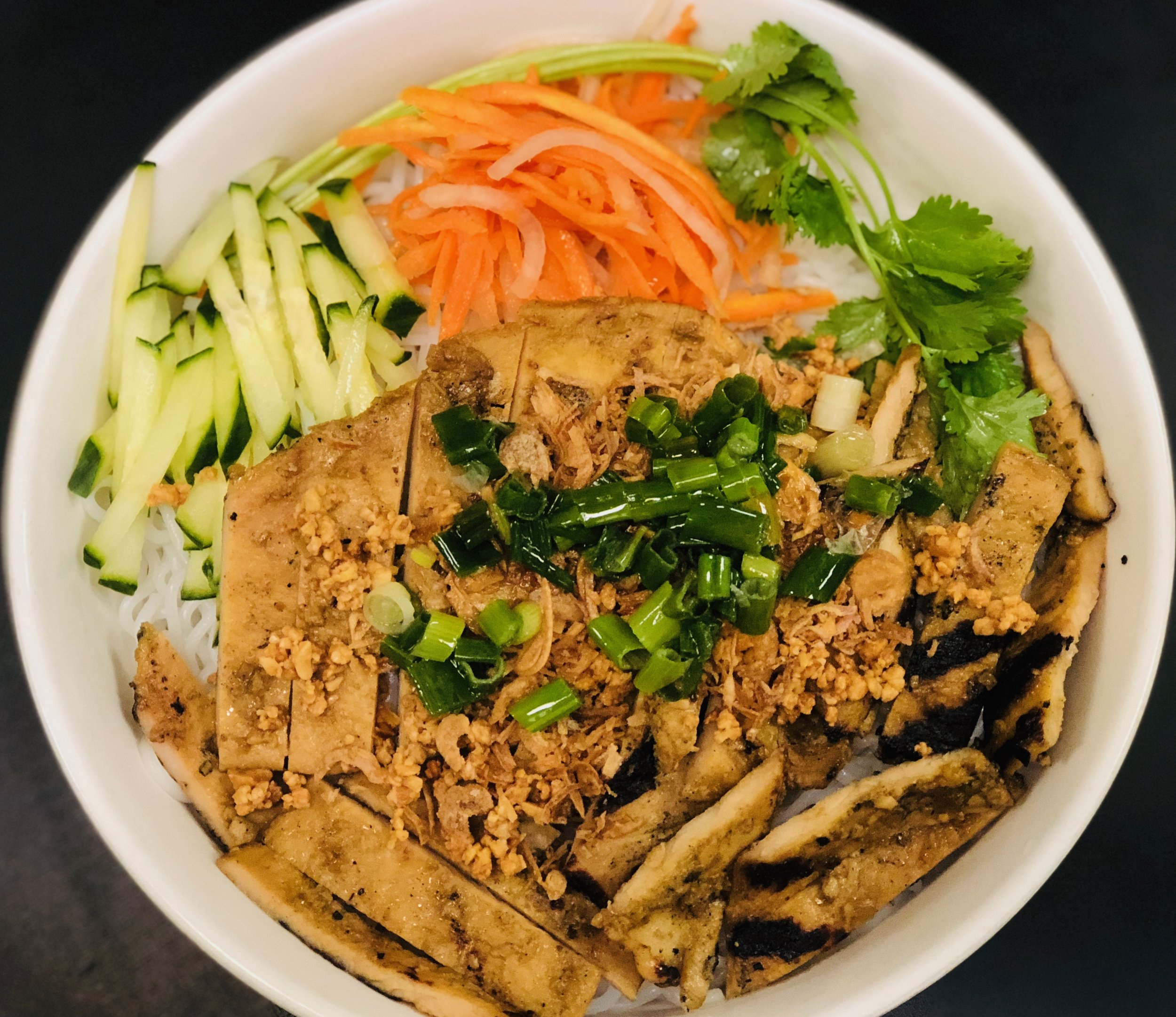 Myan's Kitchen Noodle bowl with grilled chicken. Top with fried onion, green onion, cilantro, peanut. Fresh cucumber, carrot.