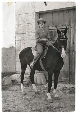 Társila riding her horse at the door of the wine cellar.