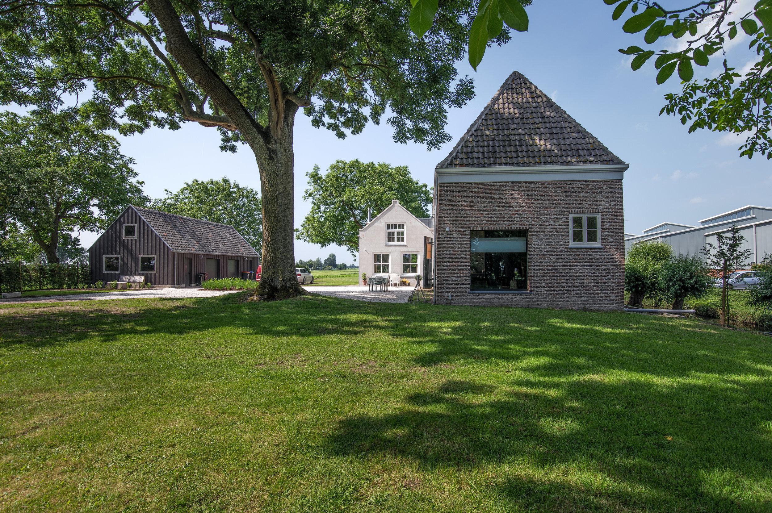 Koetshuis Benschop vanuit tuin met aanbouw en schuur