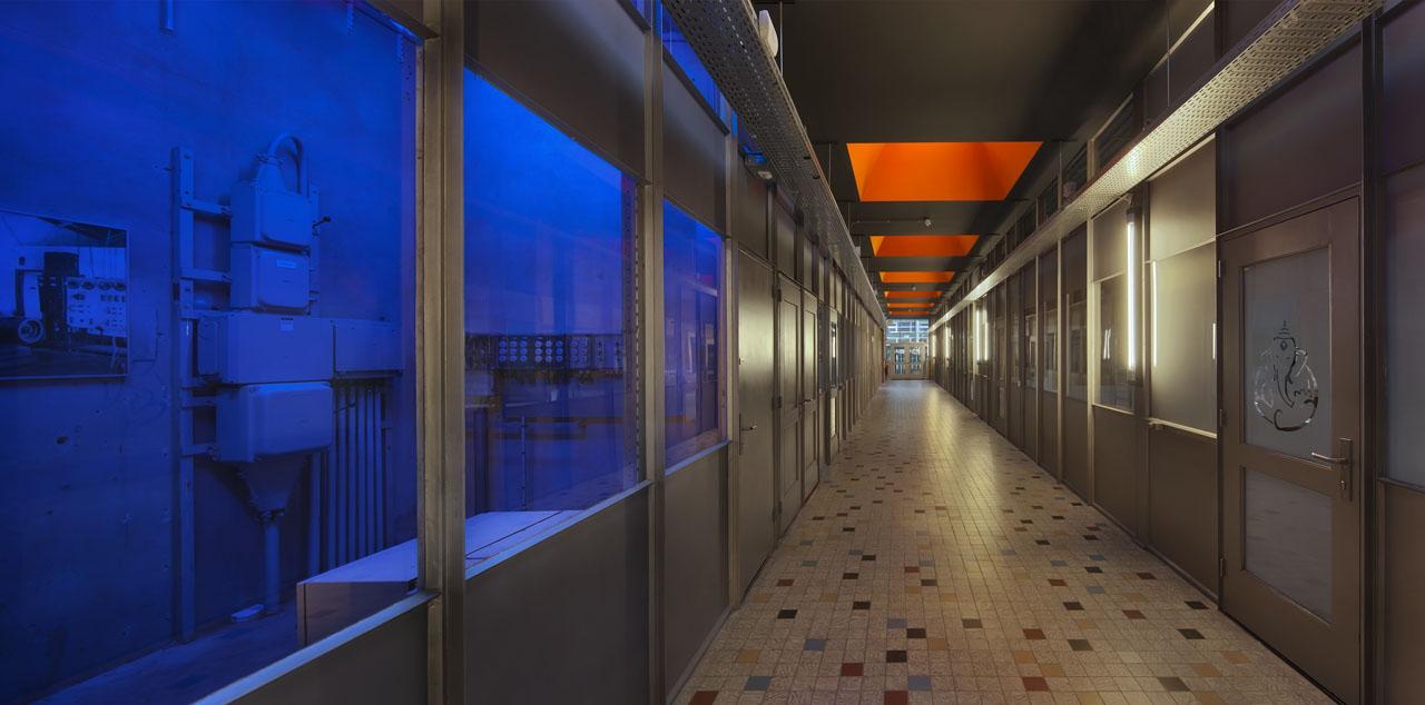 Gang van de Bedrijfsverzamelgebouw de Pionier Mitros. Industrieel interieur met oranje lichtkoepels en blauwe ledverlichting.