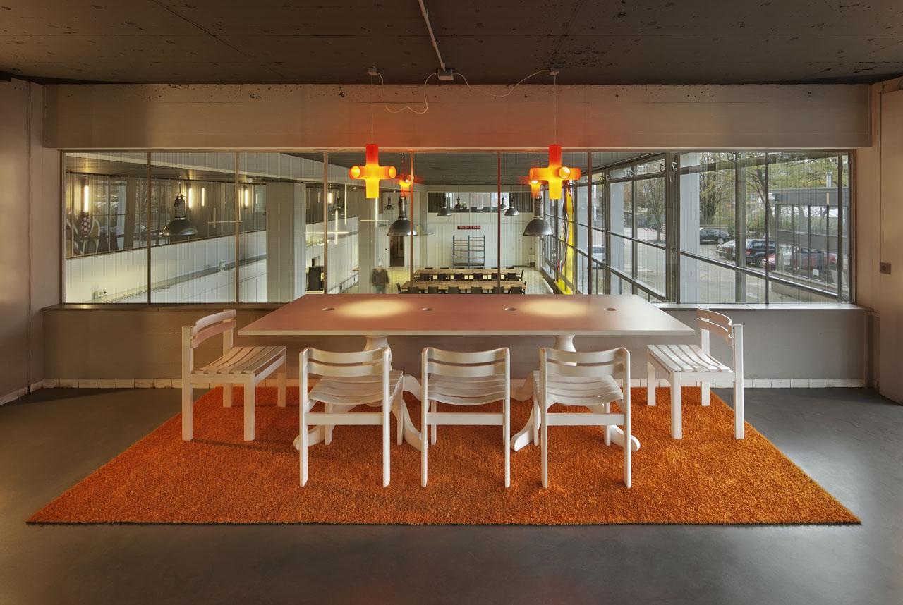 Overlegplek in interieur Pionier, gangzone. Kruislampen (crosslight) Dark en oranje grasmat.