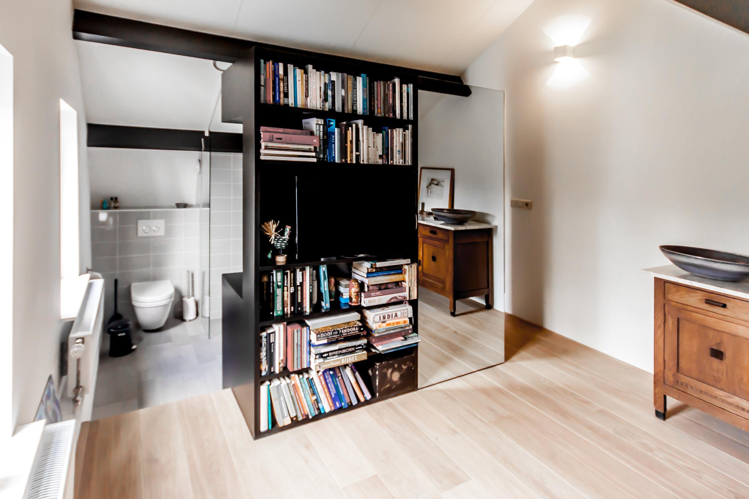 Gastenvertrek en badkamer met roomdivider meubel.
