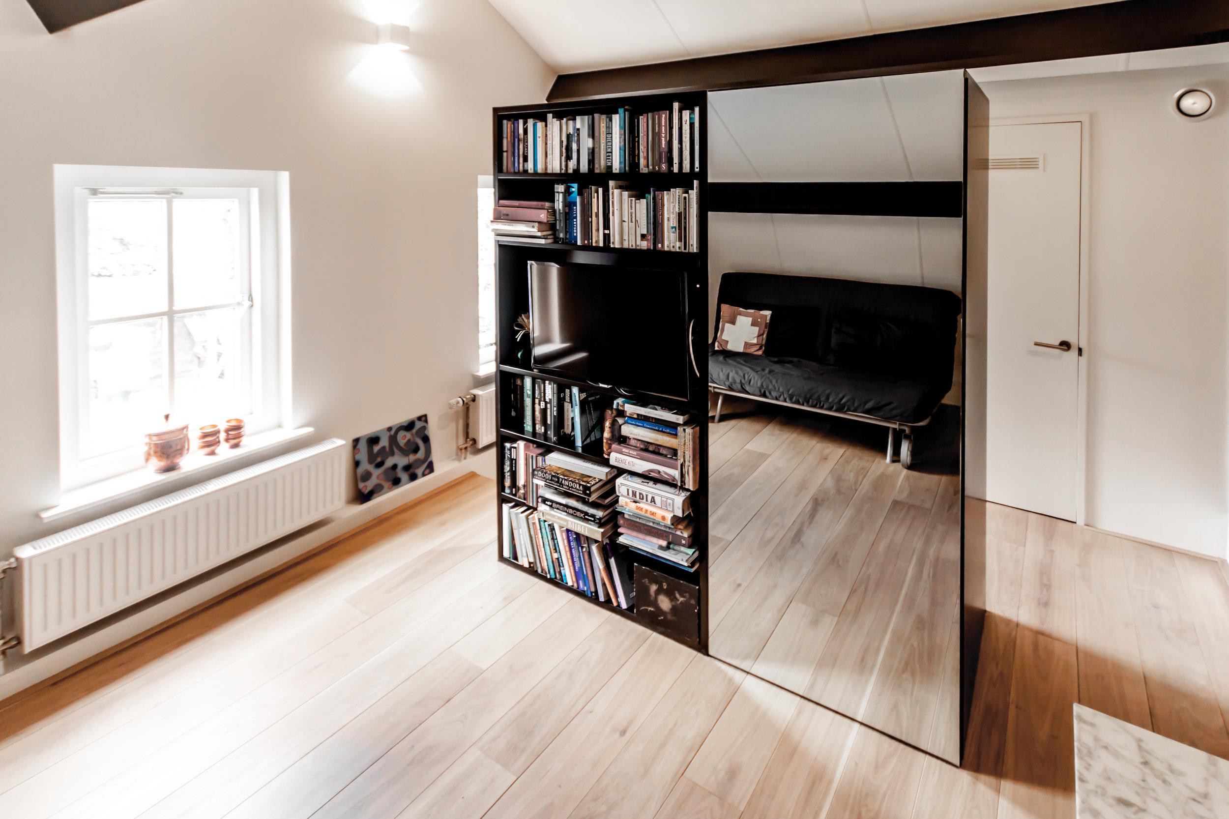 Gastenvertrek met roomdivider meubel met spiegel, boekenkast en tv.