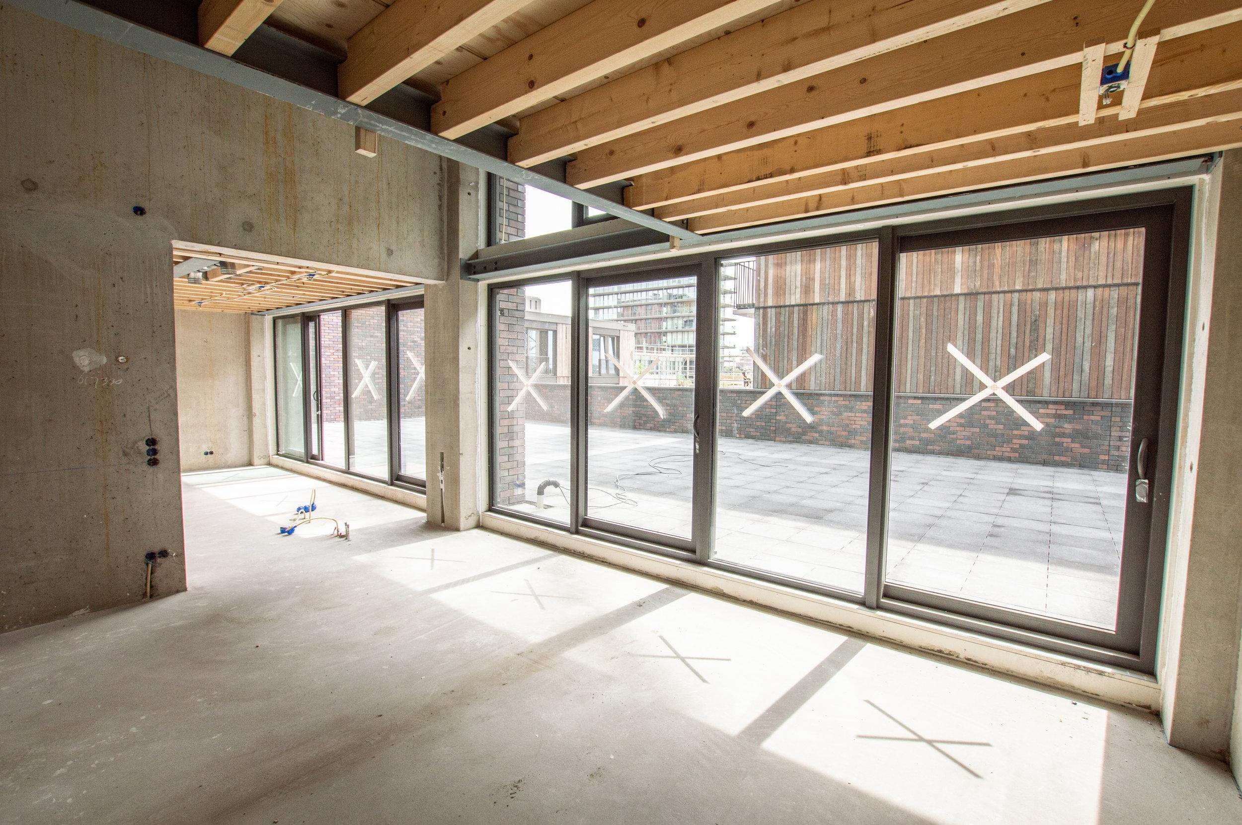 glazen pui in loftwoning met betonnen wand en betonvloer