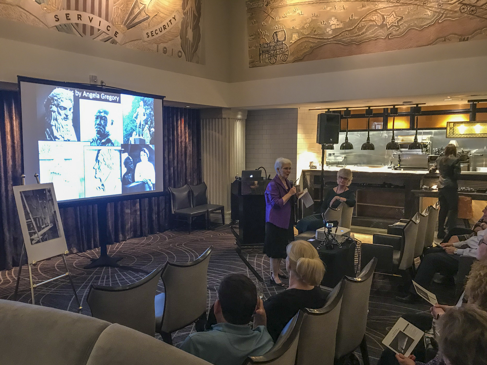 Susan Hymel, Angela Gregory historian, speaks in The Gregory restaurant, Watermark Hotel, Baton Rouge, at the launch of  A Dream and a Chisel , 7 February 2019. Sculptured murals by Angela Gregory may be seen above.