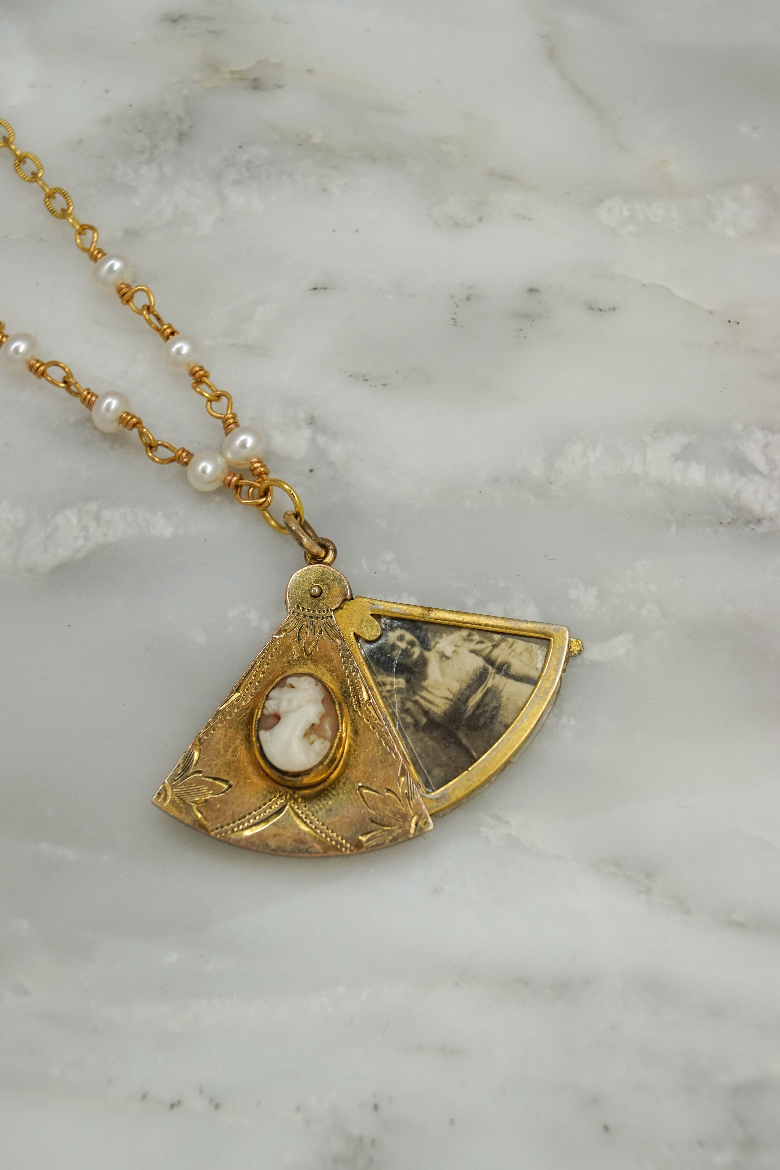 Fan-shaped gold antique locket with cameo.