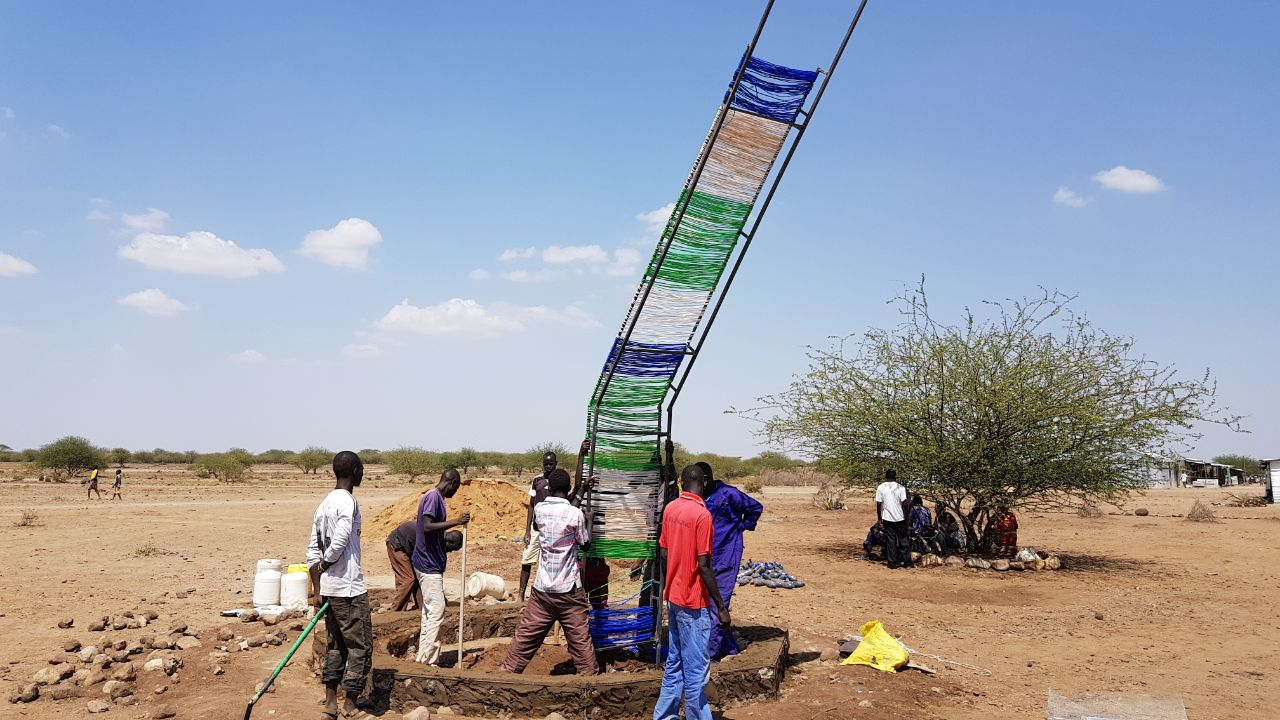 Residents build a shade structure to provide relief from the sun as the new trees grow. Credit: UN-Habitat
