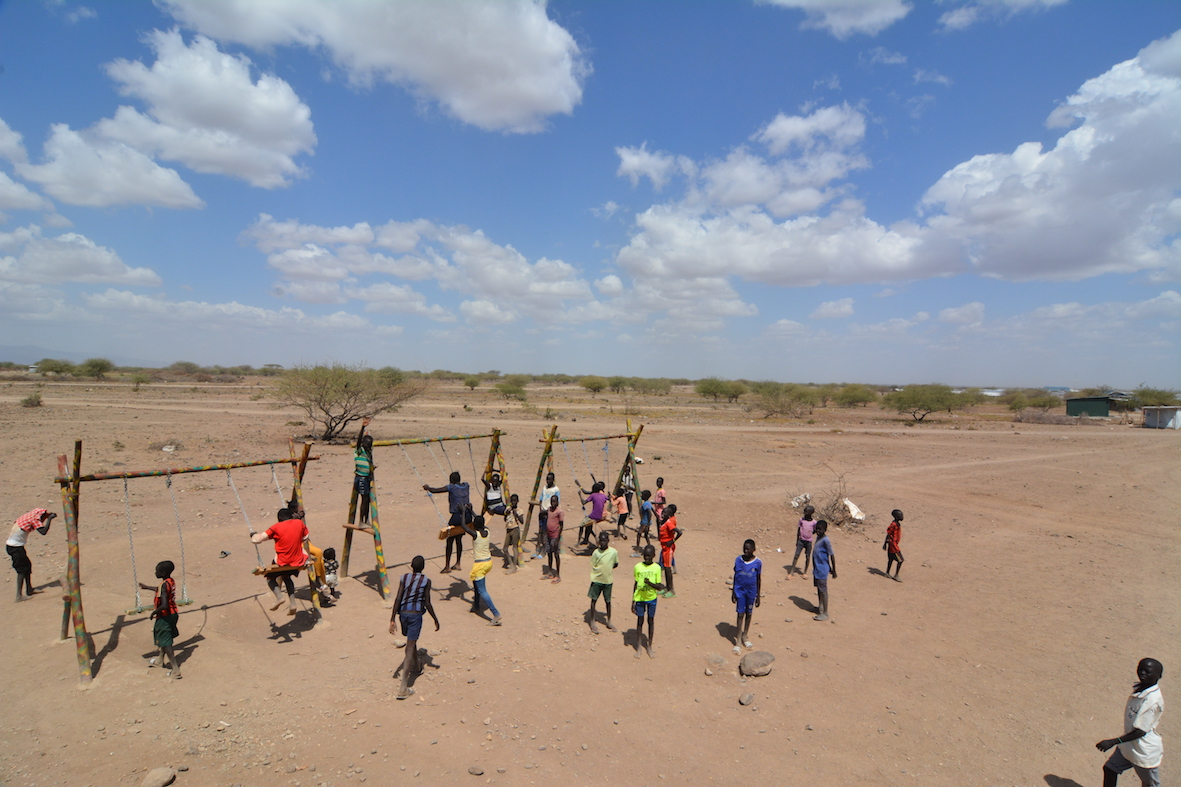 Locals play on the (very popular!) new swing set at the Village I site. Credit: UN-Habitat