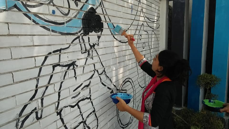 A woman helps paint new murals on the surrounding playground walls. Credit: UN-Habitat