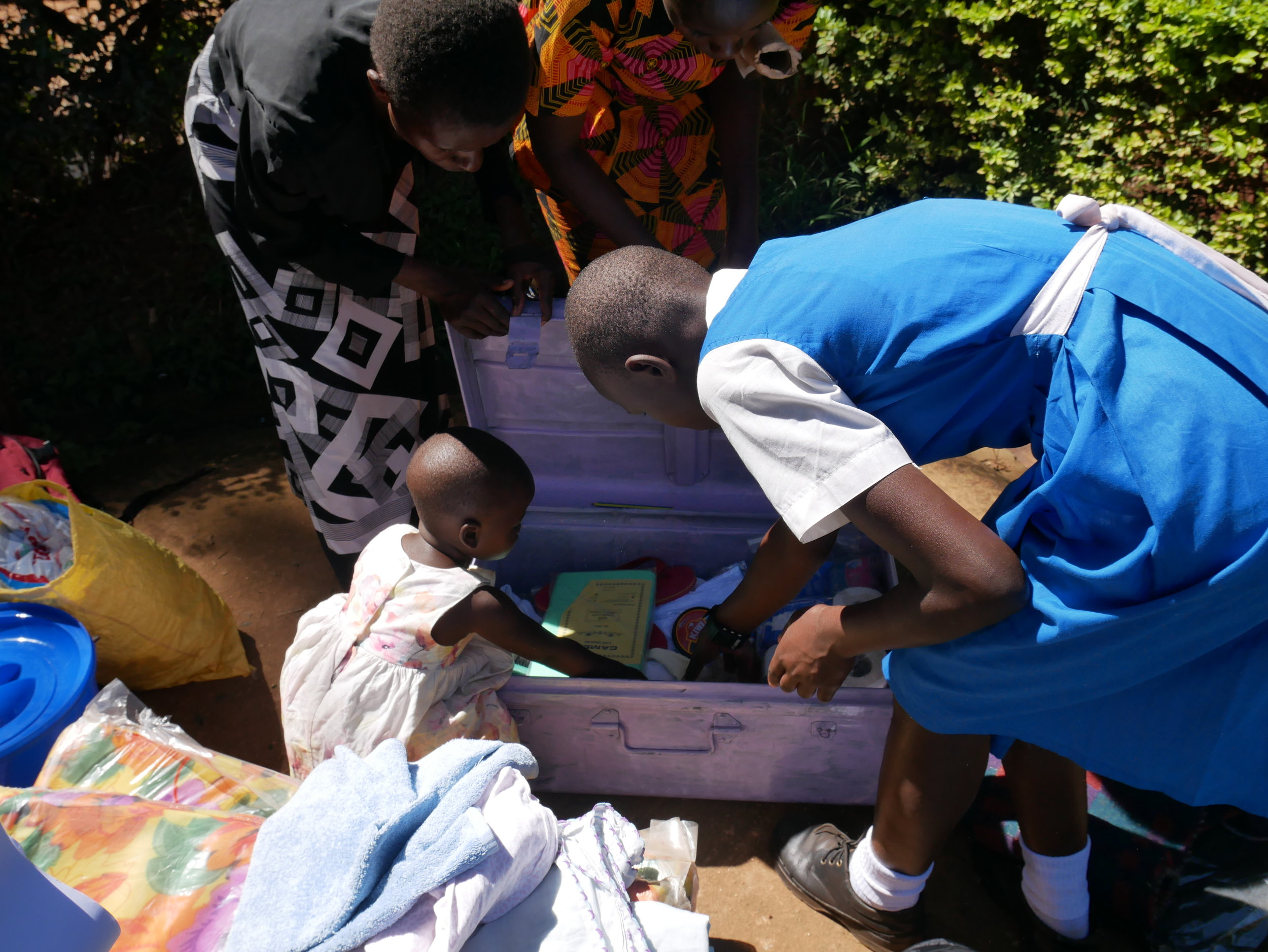 Our student Ruphine packs her school trunk with the help of her mother, aunt, and little sister.