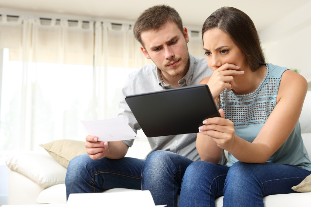 worried-couple-checking-bank-account-online-picture-id623211814.jpg