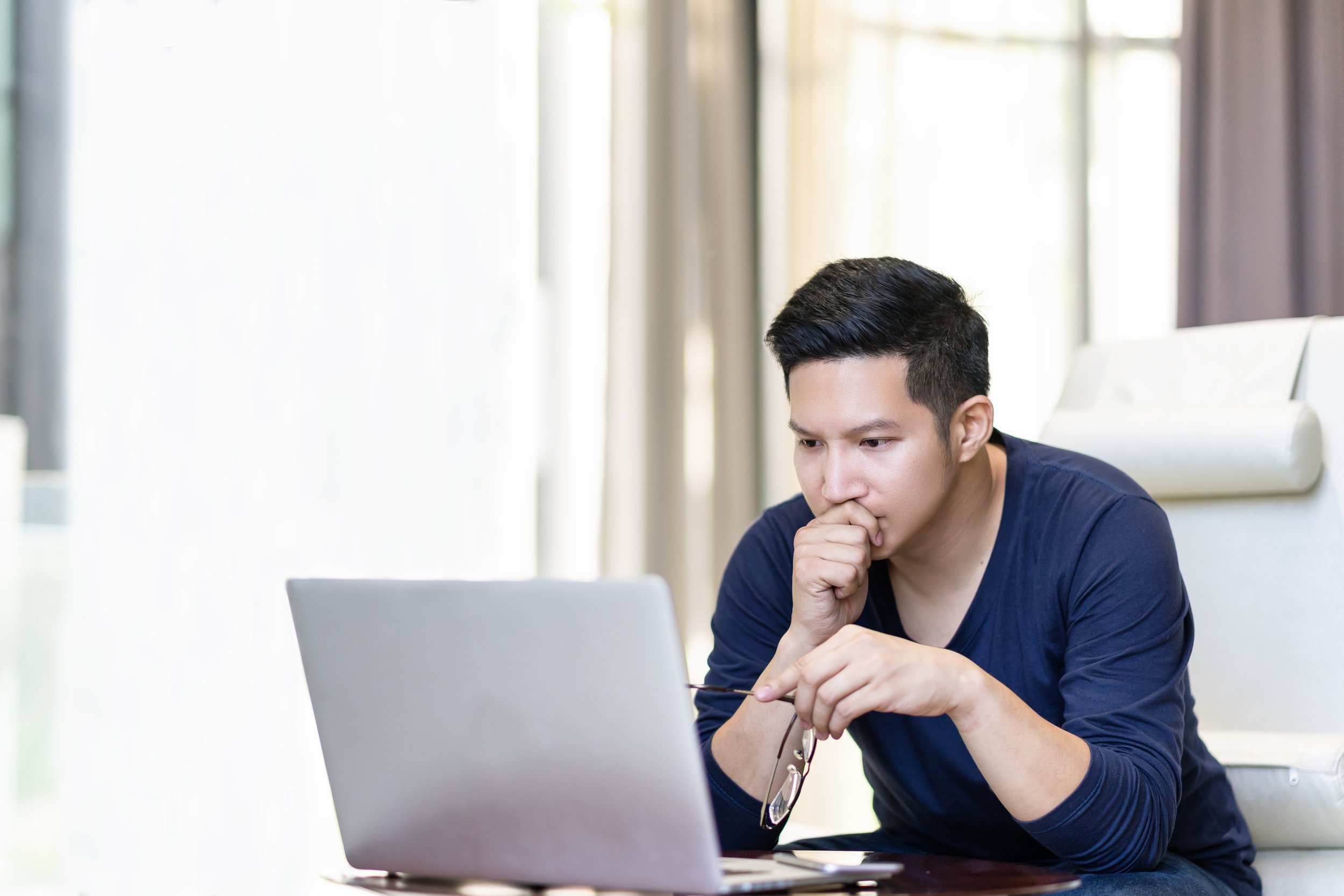 seriously-confident-asian-young-freelancer-in-smart-casual-working-and-concentrated-on-laptop-sitting-on-desk-in-modern-office-,co-working-space-or-at-home-with-copy-space,-webinar-over-the-internet-941051088_3869x2579.jpeg
