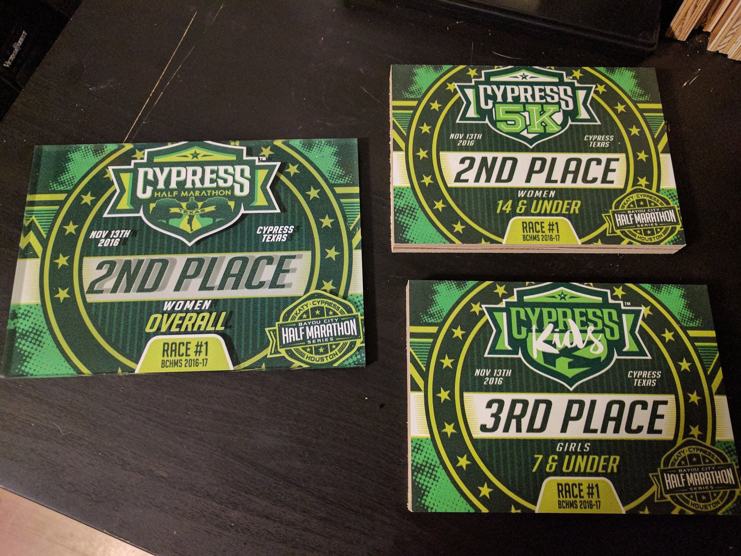 2016 Cypress Half Marathon, 5k, and kids 1k age group awards. Half Marathon awards are double-sided print on acrylic. The background is printed on the underside and the top level has the event logo, series logo, and text. The 5k and kids 1k awards are full color printed on MDO.