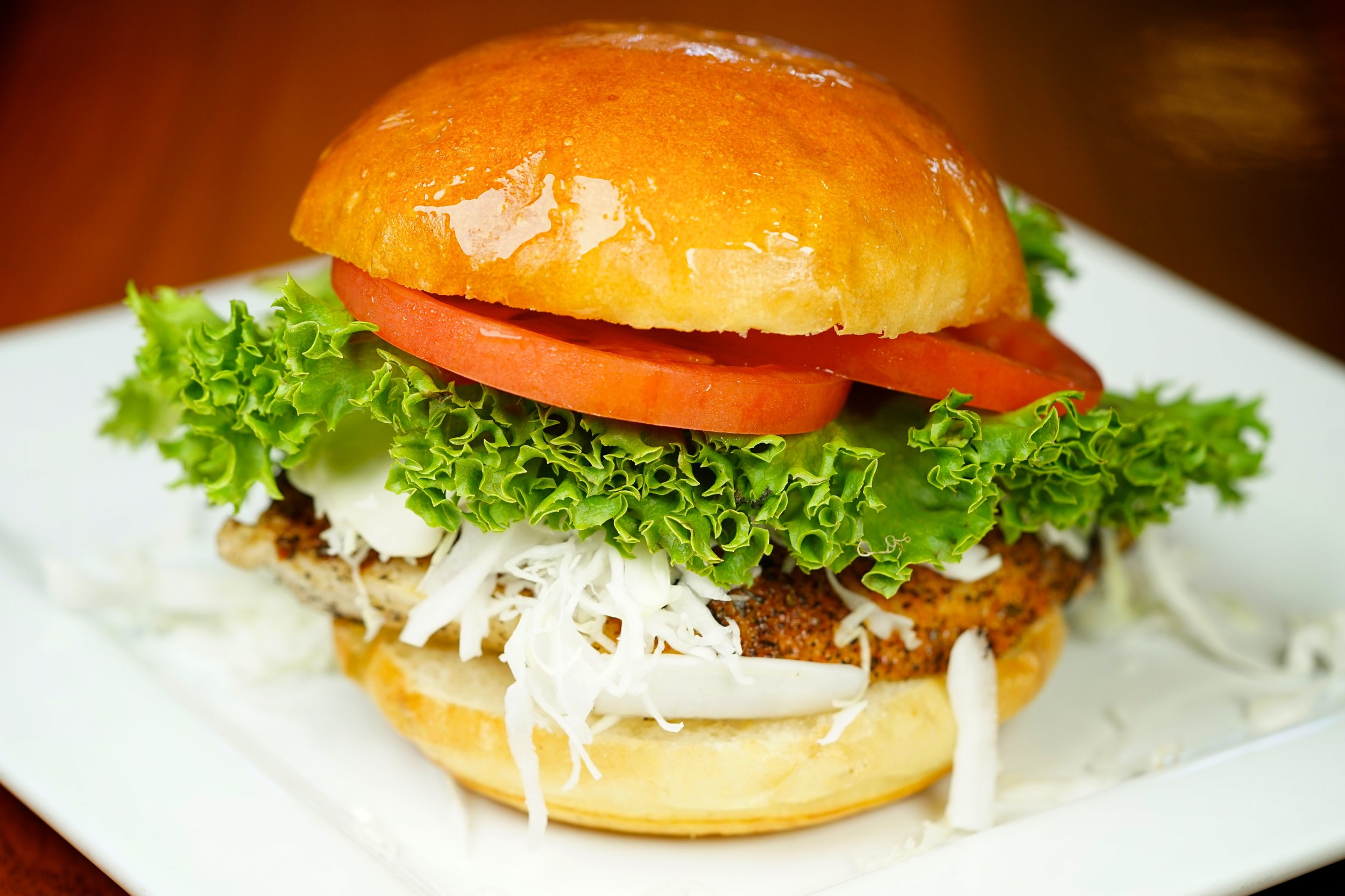 Baja Fish Sandwich - Served with shredded cabbage and our 'Kicked up' citrus jalapeno sauce. (lettuce & tomato optional)