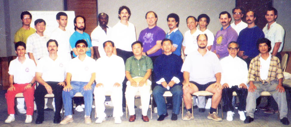 1992 – The Members of the International Baguazhang Research and Teacher's Exchange, Gather for a group photo in Houston, Texas.  Sitting (Left to Right) : Gary Stier, John Painter, Johnny Lee, George Xu, Zhang Jie, Alex Wang, Kumar Frantzis, Albert Liu, and Wei Lun Huang.  Standing (Left to Right) : (?), Lin Chih-Young, (?), Russell Sauls, (?), John Bracy, John Lebourgeois, Andrew Garza, Daniel Lee, Andy James, Joe Crandall, Richard Peck, Jerry Alan Johnson, and Dan Miller.  Other members (not shown) in attendance include : Bok Nam Park, Nick Gracenin, Chien-liang Huang, Sam Masich, Liang Shou Yu, Grace Wu, Zhang Lu Ping, Wei Lun Choy, Joe Dunphy, Kevin Gimberg and Glen Guerin.