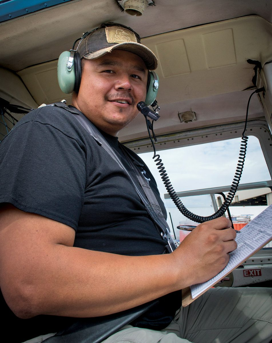 Paul Betsina jumped at the chance to take part in a helicopter survey as a technician. He recorded data about boreal wetlands while sharing knowledge of the land with his survey crew. ©DUC