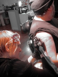 Alice Kendall tattooing a brook trout on Tommy Habetz