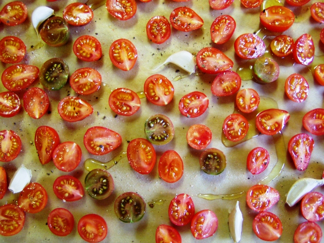 I sliced up a couple trays worth of cabernet and chocolate cherry tomatoes last weekend and slow roasted them with garlic and olive oil. I took this, of course, before I put in the oven.