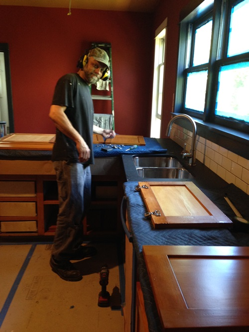 Clarence Jacobs installing the cabinets he made from the CVG Doug Fir bleachers.