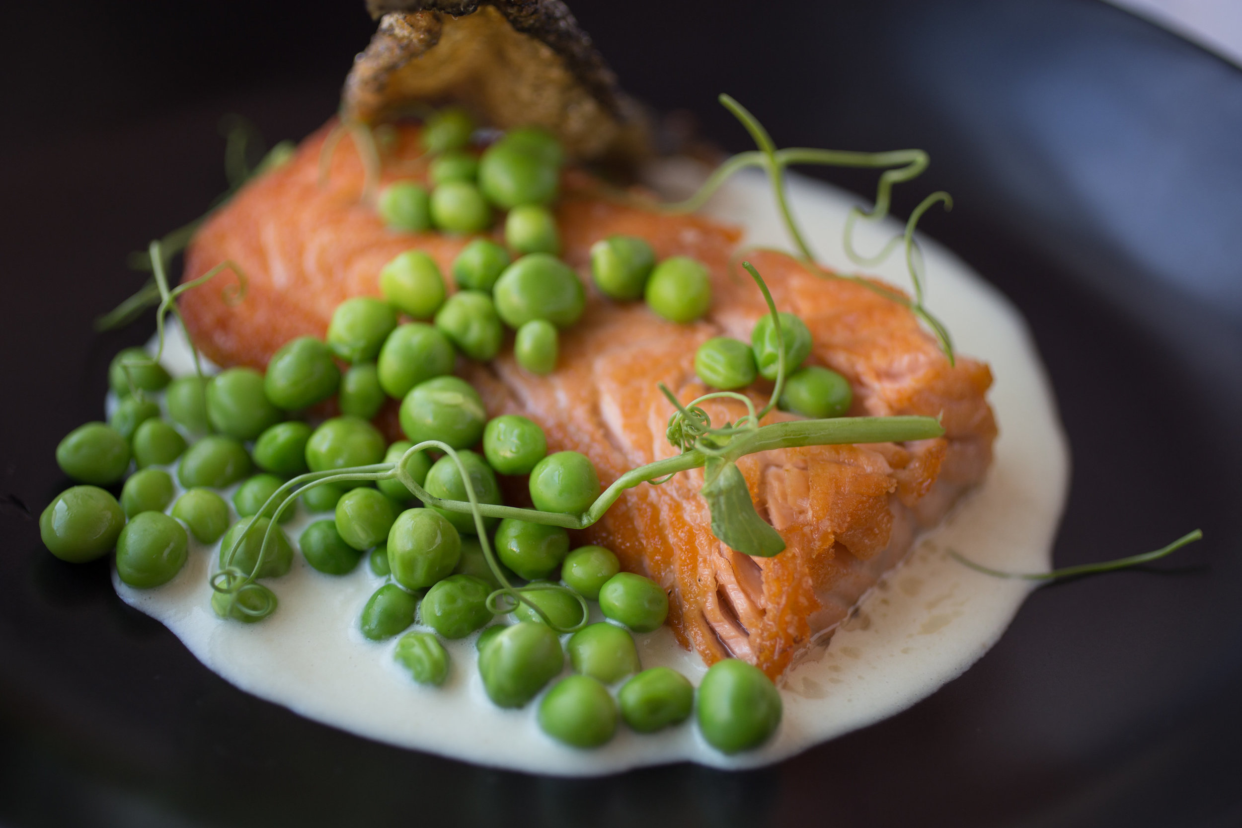 Chef Orlando Amaro  presents Seared Salmon (english peas, peas shoots, soubise sauce, salmon crackling). 📸  @ebradyrobinson  /  @bmoreculinary