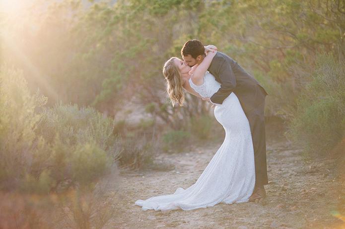 Anza-valley-wedding-at-the-alpaca-farm-groom-kissing-bride-at-sunset.jpg