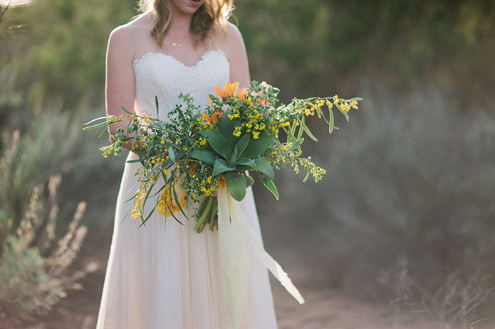 Anza-valley-wedding-at-the-alpaca-farm-bride-holding-green-and-yellow-floral-bridal-bouquet.jpg