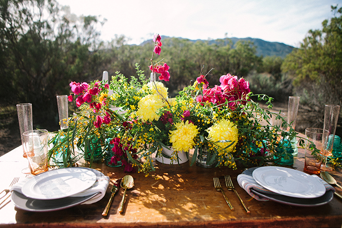 Anza-valley-wedding-at-the-alpaca-farm-brown-wood-table-with-white-place-settings-and-pink-and-yellow-flower-centerpiece.jpg