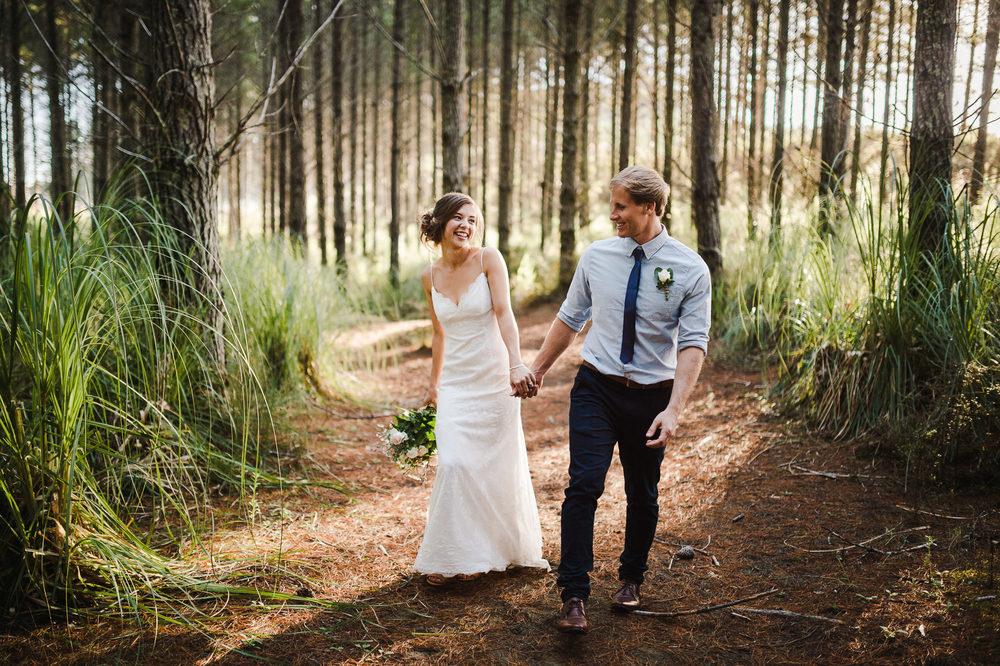 bride+and+groom+walking+through+forest+auckland+wedding.jpg