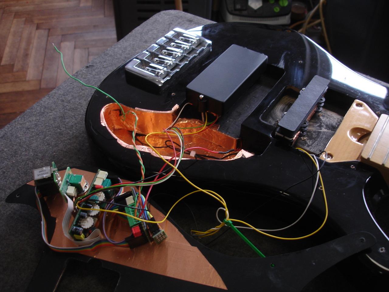 - Als die Abnehmer da waren, montierte ich Elektronik und Abnehmer auf das spezielle Schlagbrett und mir wurde klar, um diese Elektronik vernünftig einzustellen, muss man erstmal, um mehr Platz zu haben, die Buchse seitlich anbringen, und außerdem von hinten drankönnen. Denn man möchte ja nicht jedesmal Saiten und Schlagbrett abnehmen, um Feineinstellungen an der UNI-PRE Elektronik vornehmen zu können.