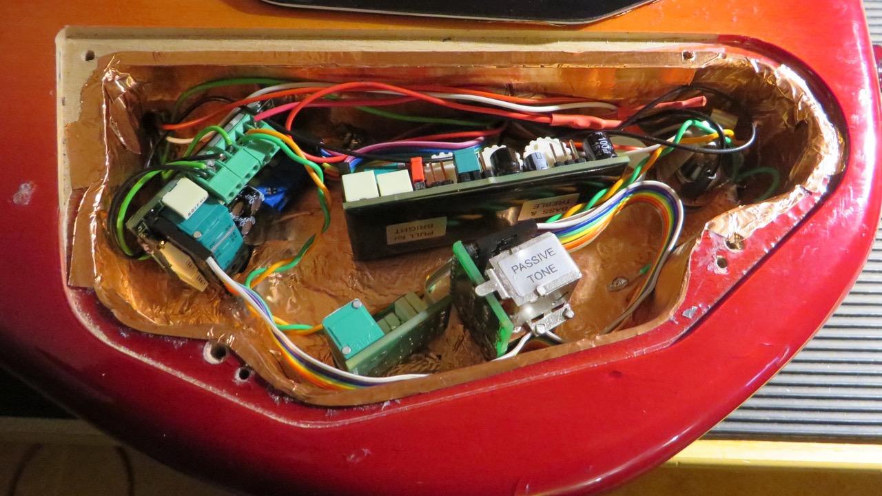 - Nun wird die East Elektronik eingebaut, und die Tonabnehmer angeschlossen. Der Spieler kann den Gain der beiden Pickups selbst justieren, und die Einsatzfrequenzen der Höhen, Hoch- und Tiefbässe bei Bedarf mittlels der kleinen Drehrädchen selbst nachregeln.