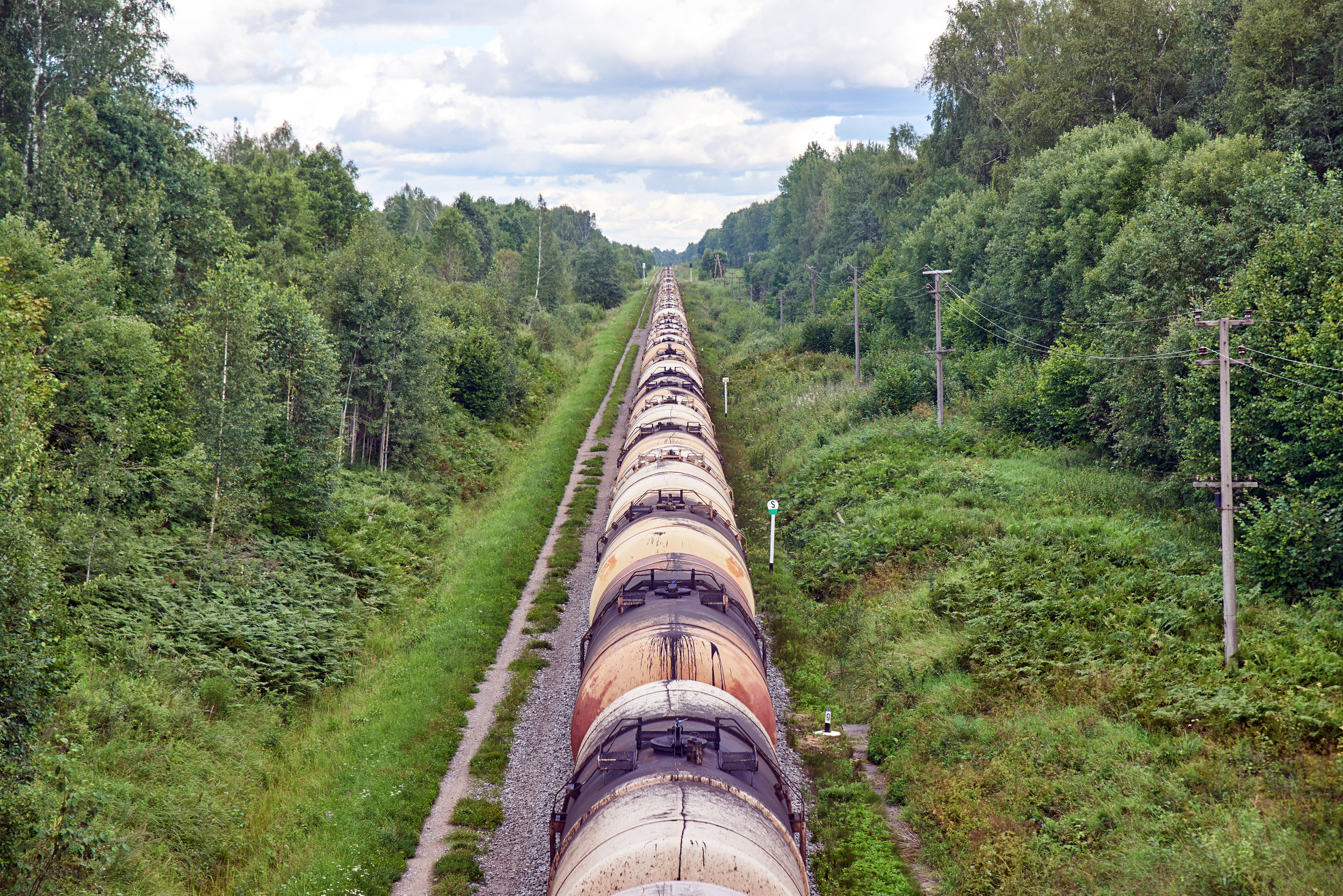 Set-of-train-tanks-with-oil-and-fuel-transport-by-rail---countryside-view-682538860_3866x2580.jpeg