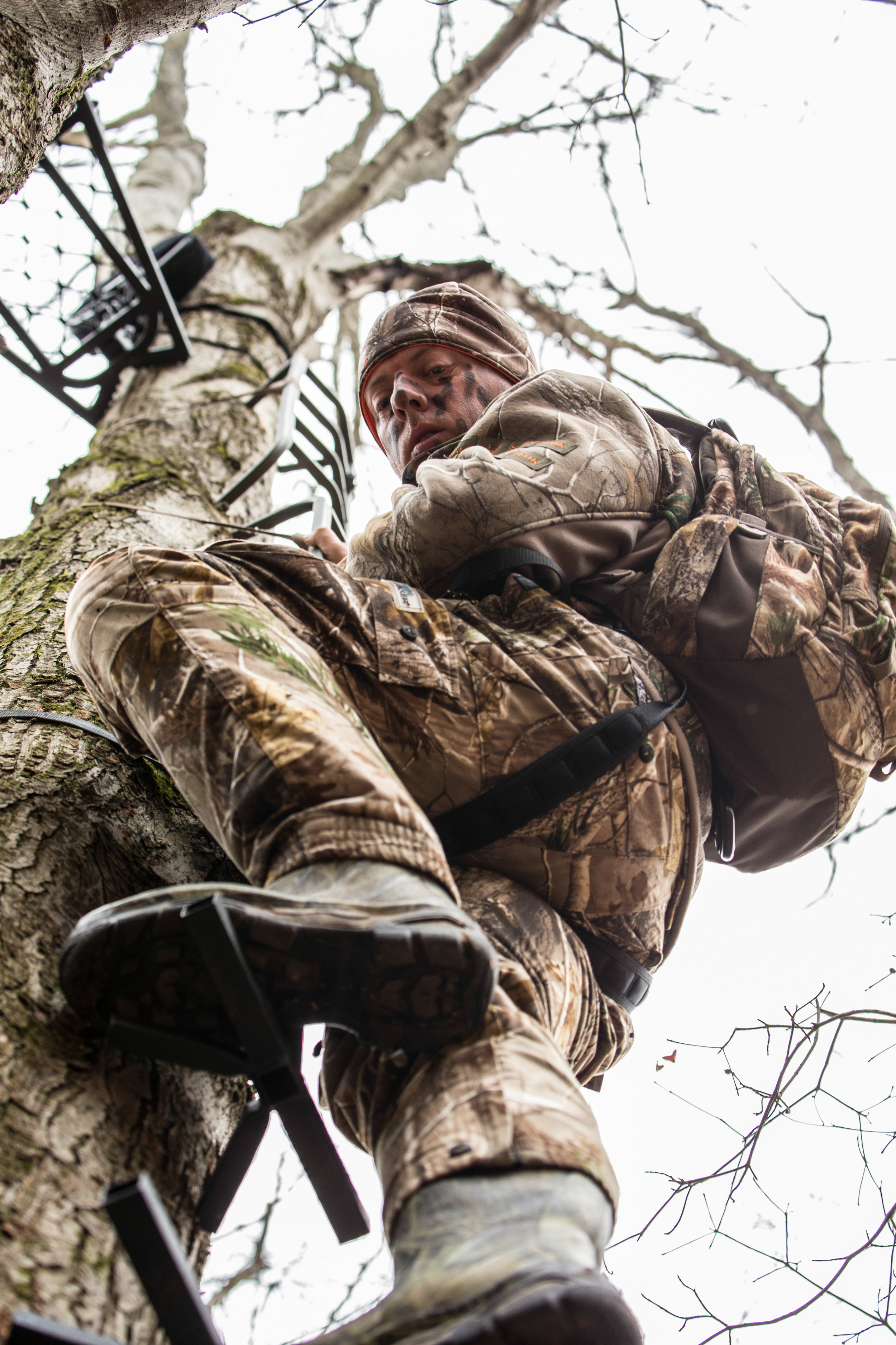 hunter looking down while climbing to treestand