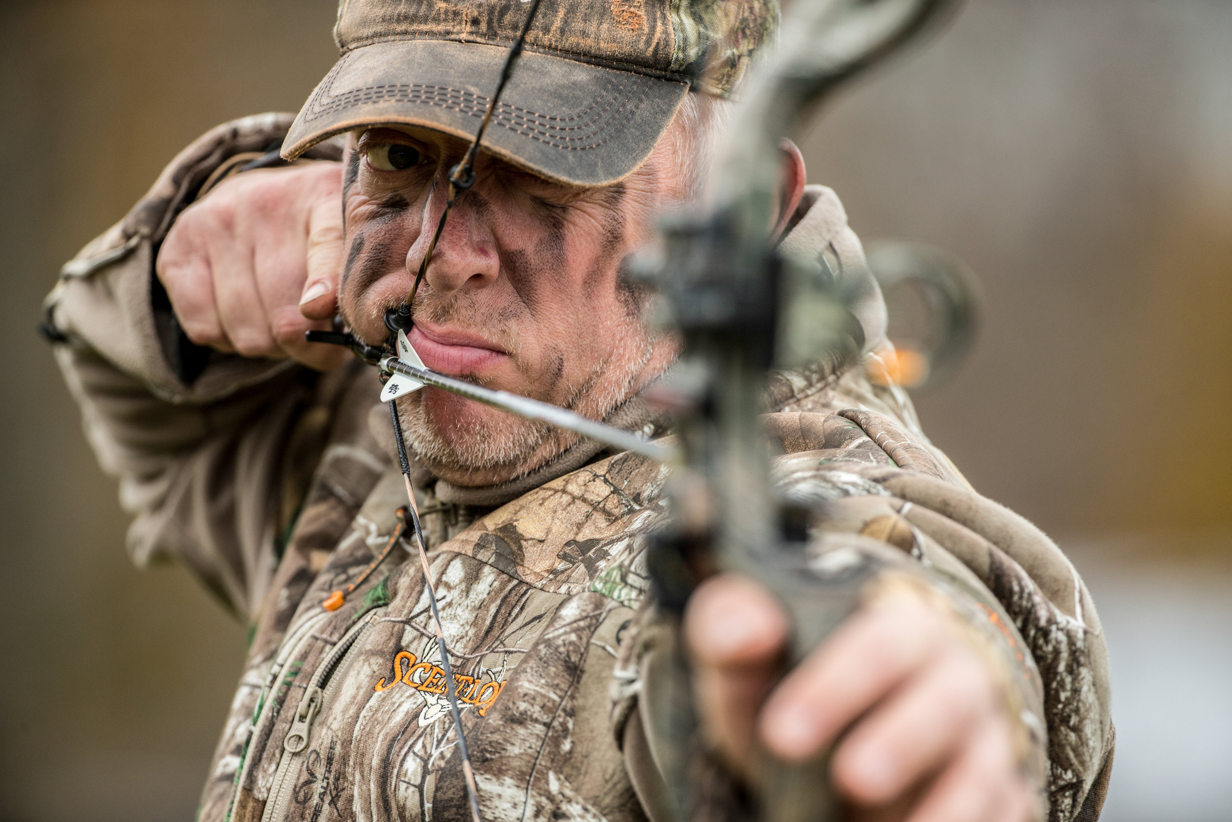 bowhunting wearing face paint at full draw
