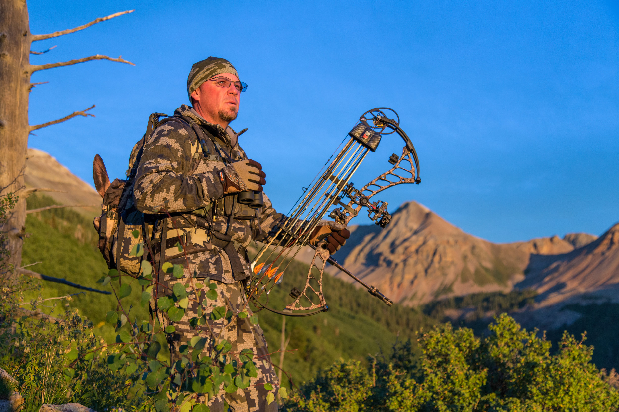 Bowhunter glassing on side of mountain