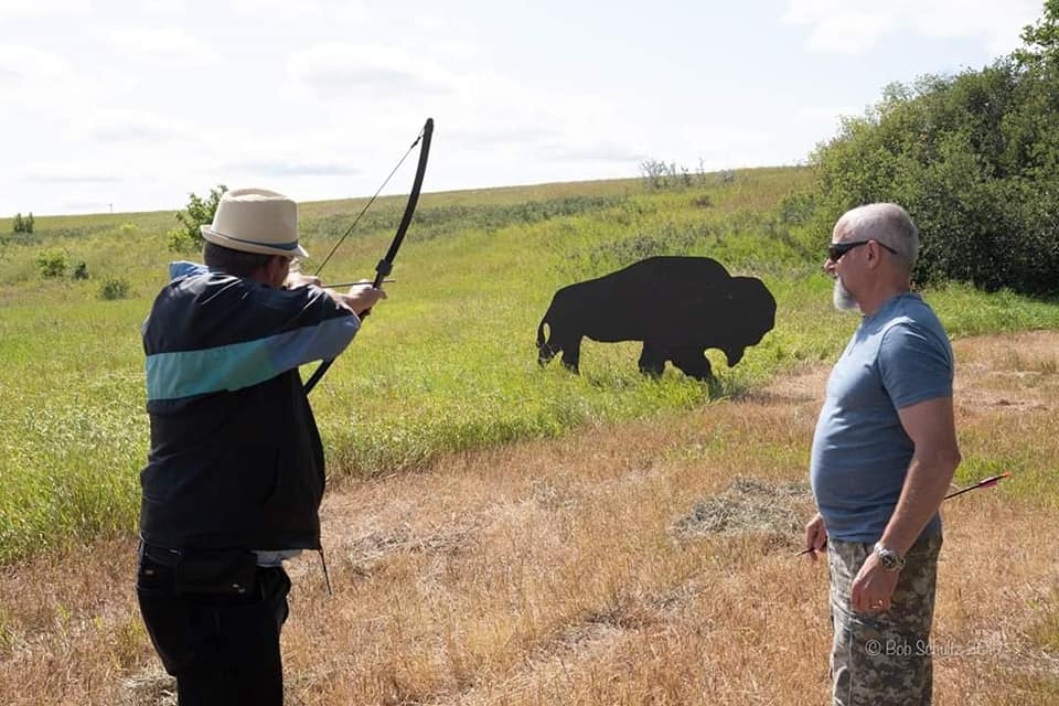 """Dale Jelinski tries his hand at hitting the target with a now and arrow. Participants could also try throwing a replica """"altal-altal"""" - Photo by Kimberly Epp"""