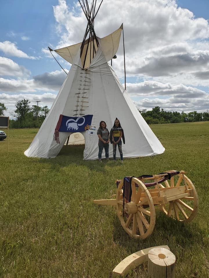 Two volunteers pose in front of the teepee and cart - Photo by Kimberly Epp