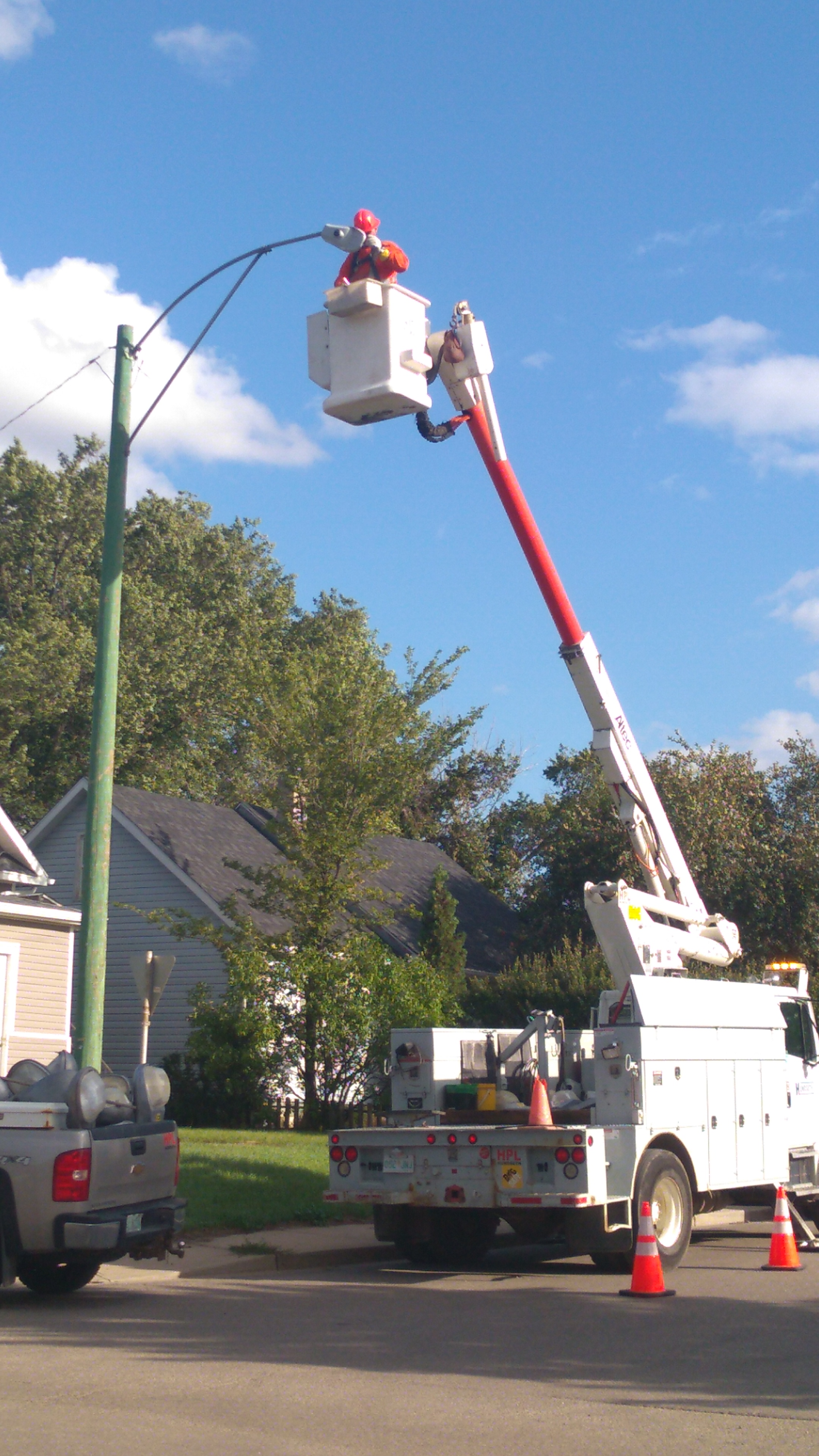 SaskPower contractor replaces street light at the corner if Redland Avenue and MacDonald Street on Monday afternoon