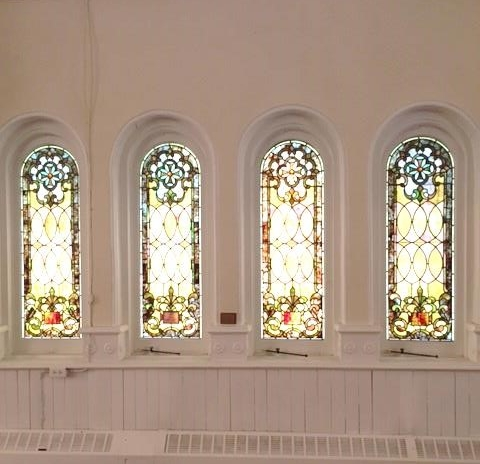 """- The four-window set of single panel windows on the west wall of the sanctuary below the """"Transfiguration"""" (Flanagan) window share in common with the Pattern Windows, the Fleur-de-lis design.However, the flower at the upper center of the panel is replaced with the Cross-of-Malta."""