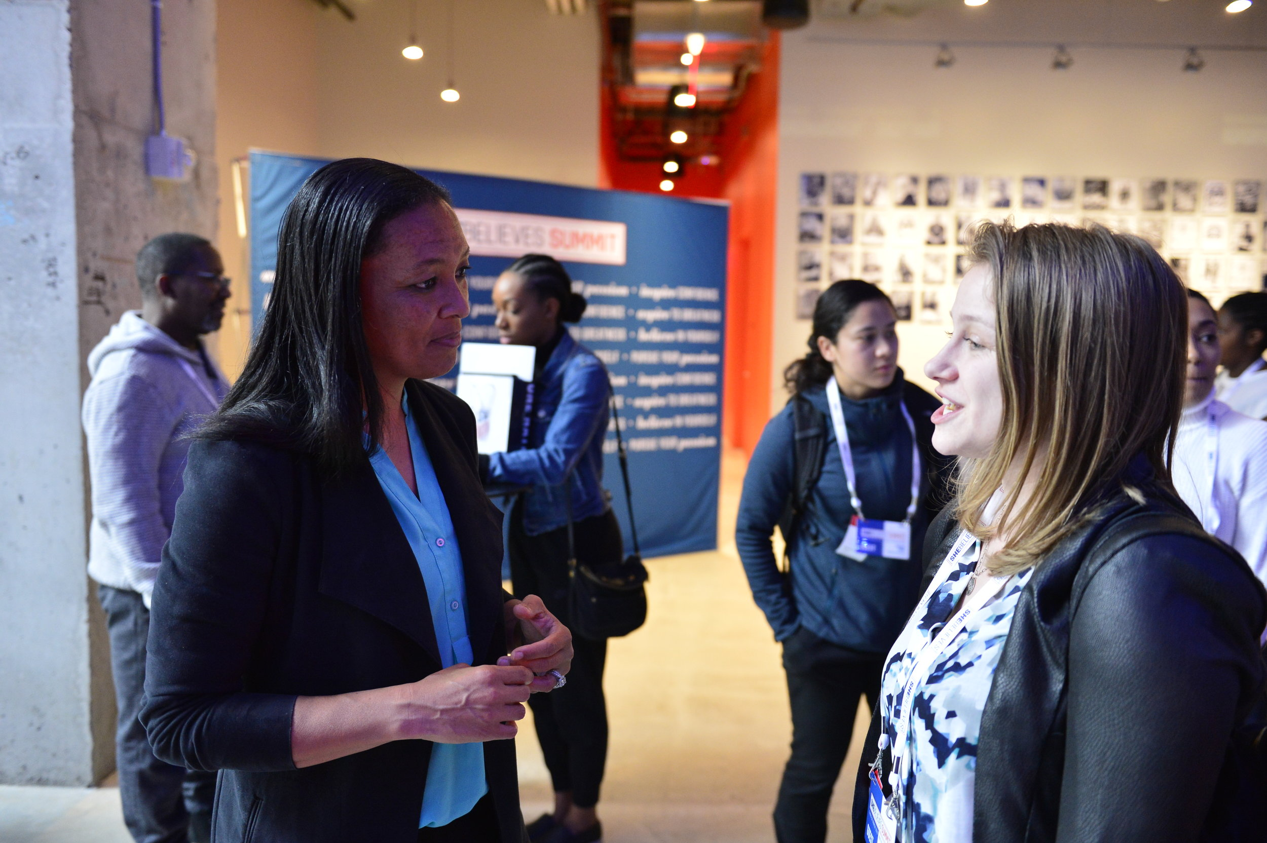 Angela Hucles speaks with a SheBelieves Summit attendee.