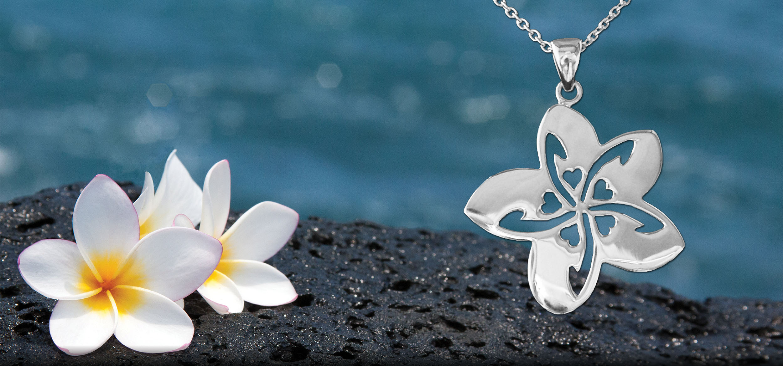 Sterling Silver Plumeria Necklace on lava rocks