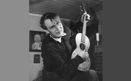 Alf Prøysen hjemme med gitar og sjarmørblikk. © NTB