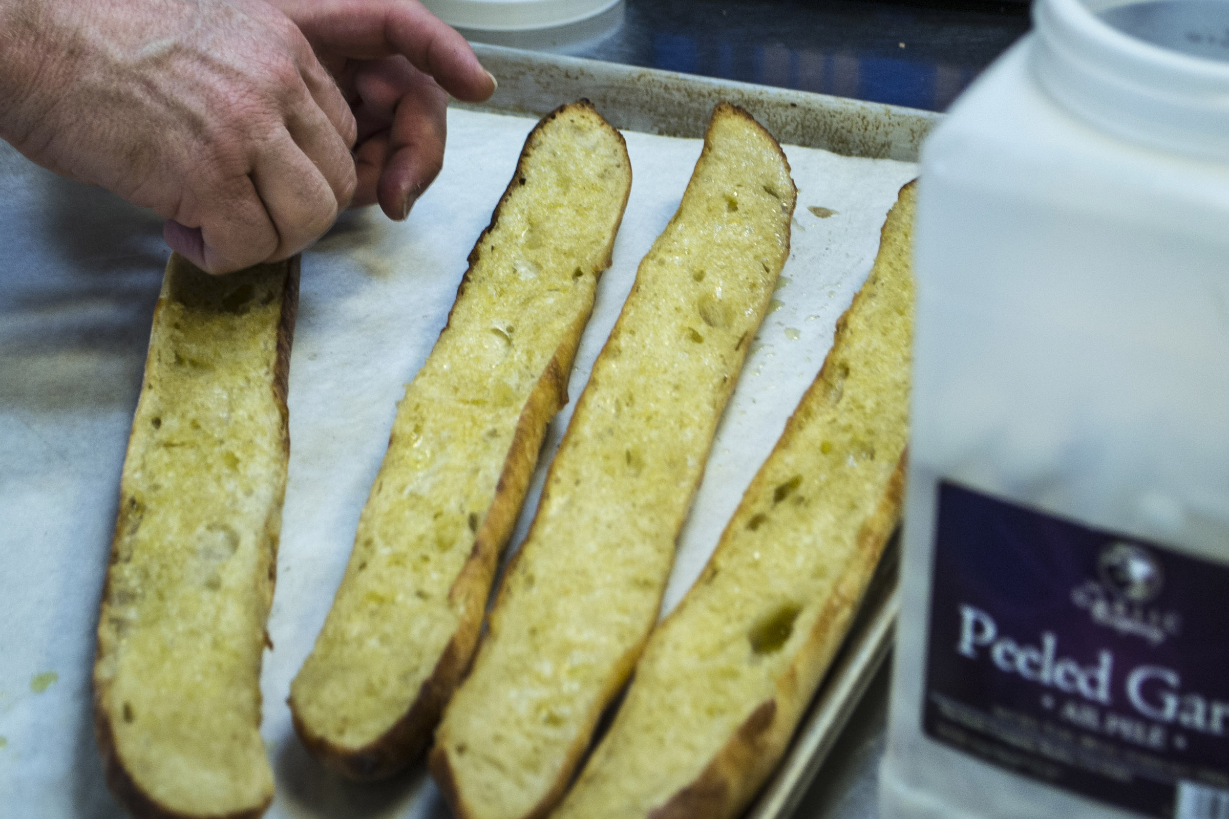 Rustic Italian Garlic Bread made by toasting Old Dog Baking Co. baguettes with olive oil and finishing off by rubbing with fresh garlic.