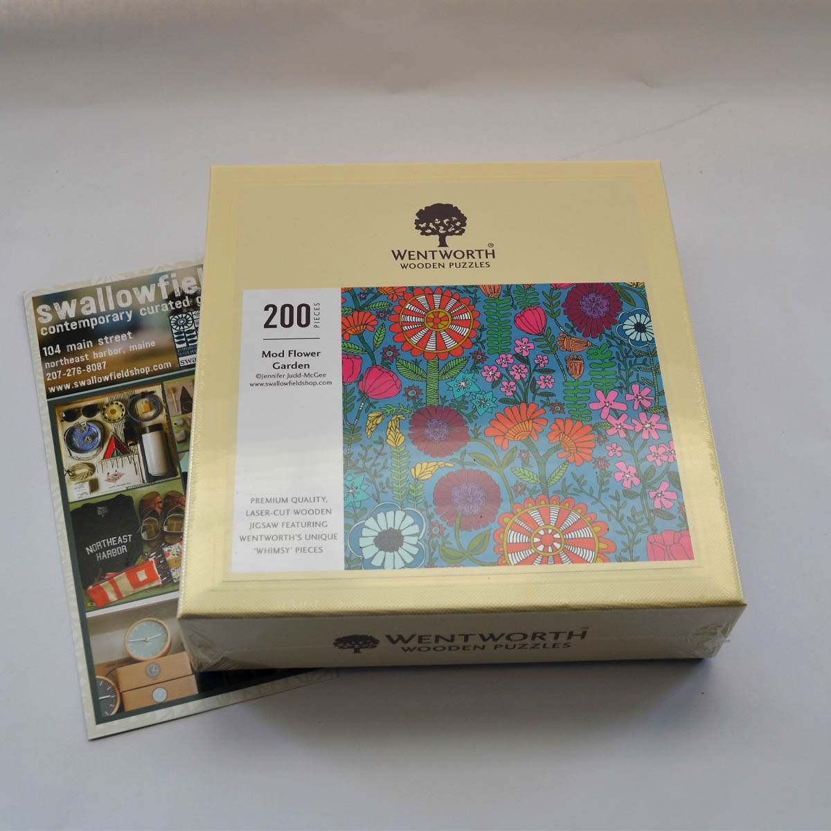 "Wooden Puzzle - Artist and proprietor of Swallowfield, Jennifer Judd-McGee not provided her artwork for this puzzle to be created, but she also generously contributed a copy to our auction as well! This 200 piece wooden ""Mod Flower Garden"" puzzle is the perfect group activity whether it's on a rainy day or just a little bit at a time over the course of the summer. You can catch more fun items like this at her Main St. shop or even shop online!"