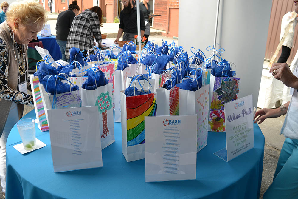 """Colorful bags were created by summer campers and used to keep each bottle of wine a """"mystery"""""""